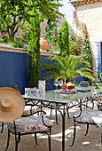 Metal outdoor furniture, palms and cypresses on terrace with blue screen wall