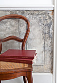 Books on antique chair with cane seat