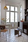 Schwarz-weiße Küche mit Tisch und zwei Stühlen in Altbauwohnung