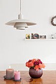 Vase of roses and two candles on wooden table below classic pendant lamp