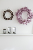 Autumnal wreaths on white wall above candle lanterns on shelf