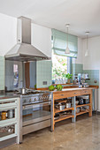 Wooden counter with drawers and open-fronted shelves combined with stainless steel appliances in kitchen