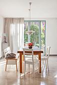 Esstisch mit weißen Stühlen und Sitzbank vor Terrassentür
