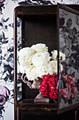 White ranunculus and a bouquet of red roses in a display case