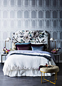 Bed with a floral headboard in front of a wallpaper with an architectural motif