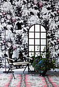 Chair and floor mirror against opulent floral wallpaper
