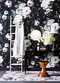 Ladder and dressing table in front of dark floral wallpaper