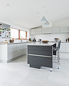 Modern grey-and-white kitchen-dining room with sloping ceiing
