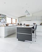 Moderne Wohnküche in Weiß und Grau unter der Dachschräge
