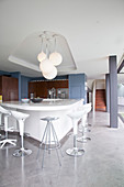 Various bar stools around futuristic kitchen island