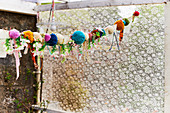 Girlande aus Pompons, Stoffresten und Stoffblüten
