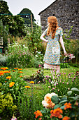 Red-haired woman wearing floral dress in garden