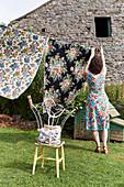 Frau im Blümchenkleid bei Wäscheaufhängen im Garten