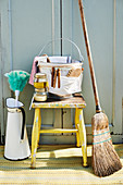 Bucket of cleaning utensils on stool with besom broom and feather duster