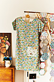 Floral summer dress on coat hanger and fabric swatches