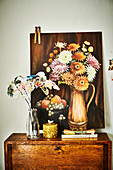 Glasflasche mit Stoffblumen auf Kommode, Bild mit Blumenstillleben an die Wand gelehnt