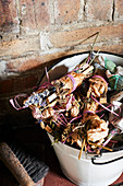 Bundles of kindling and herbs tied with raffia in bucket