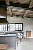 Open-plan, industrial-style kitchen-dining area with high ceiling