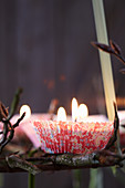 Suspended Advent wreath made from branches decorated with candles in paper cake cases (close-up)