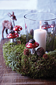 Candle lantern in moss wreath decorated with pine cones and toadstool ornaments