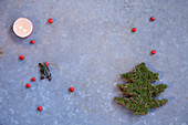 Festive arrangement of tealight, berries and Christmas tree made from moss