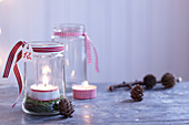 Festive, DIY candle lanterns decorated with moss and ribbons