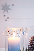 Festive arrangement of candle and pine cone in mason jars decorating with garland of stars