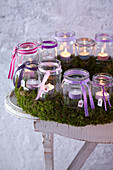 Advent calendar made from tealights jars in moss wreath