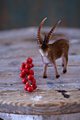 Rustic winter arrangement of ibex figurine and sprig of red berries