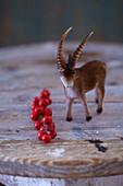 Steinbock-Figur und roter Beerenzweig als rustikal winterliche Dekoration