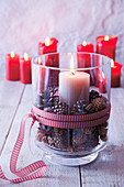 Festive arrangement of pillar candle and pine cones in glass vase on table
