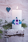 White pillar candle festively decorated with ribbon and star