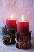 Two red pillar candles festively decorated with moss, pine cones and cinnamon sticks