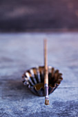 Paintbrush lying across metal tart case