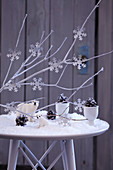 Wintry landscape made from artificial snow, polar bear figurine, pine cones and snowflake decorations on branches