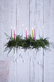 Suspended Advent wreath made from asparagus leaves decorated with candles and white-painted nuts