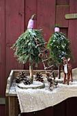 Small trees handmade from conifer branches and slices of tree trunk as wintry garden decorations