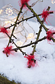 Handmade twig star and fairy lights in snow