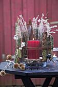 Windlicht winterlich dekoriert mit Naturmaterialien auf Gartentisch