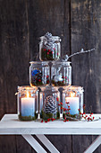 Pyramid of festive mason-jar candle lanterns decorated with natural materials