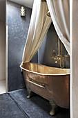 Freistehende Badewanne aus Kupfer mit Baldachin in einer Nische