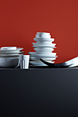 Stacked crockery, beaker and horn against red background