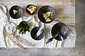 Feathers and crackers in black bowls on table