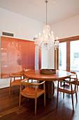 Runder Designer-Esstisch mit Armlehnstühlen, darüber Kronleuchter