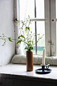 Candlestick and flowering branches in ceramic bottle on windowsill