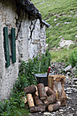 Firewood, axe and wheelbarrow outside Alpine cabin