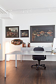 Oil paintings on wall above desk