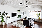 Black leather couch, sideboard, TV and houseplants in living room with white wooden panelling