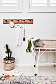 Coat rack on wall above potted cactus, wicker cot and wooden toys on floor