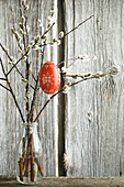 Red-painted Easter egg hung from pussy willow branches in bottle